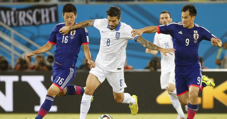 Grego Panagiotis Kone protege a bola entre dois jogadores japoneses