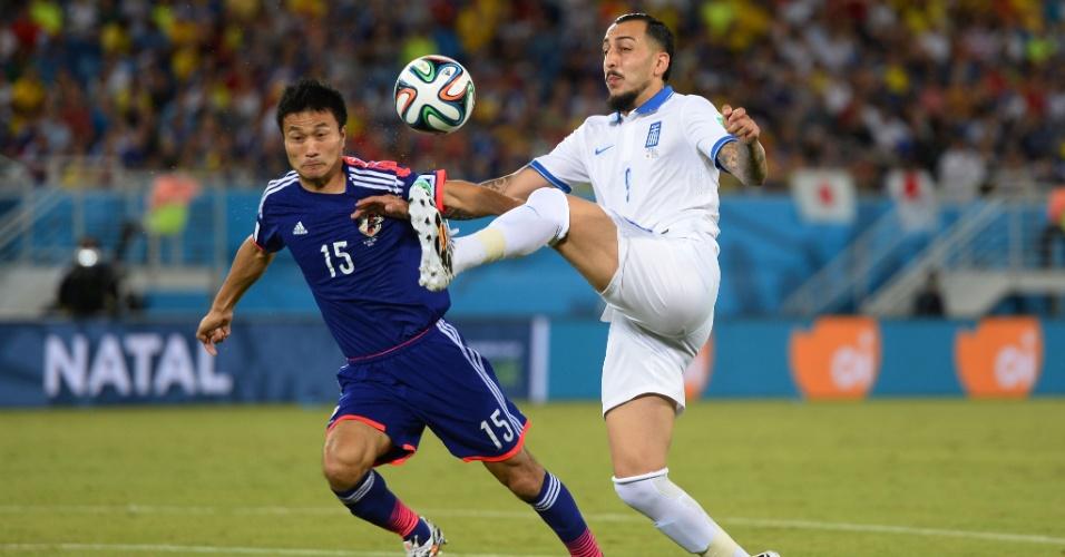 Konstantinos Mitroglou, da Grécia, estica o pé para dominar a bola enquanto é observado por Yasuyuki Konnom, da seleção japonesa