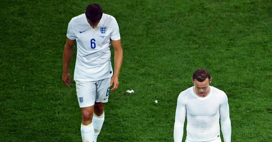 19.jun.2014 - Phil Jagielka (esquerda) e Wayne Rooney deixam o gramados cabisbaixos após a derrota da Inglaterra no Itaquerão