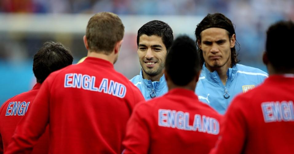 19.jun.2014 - Titular do Uruguai, Luis Suárez sorri ao cumprimentar jogadores ingleses antes do jogo no Itaquerão