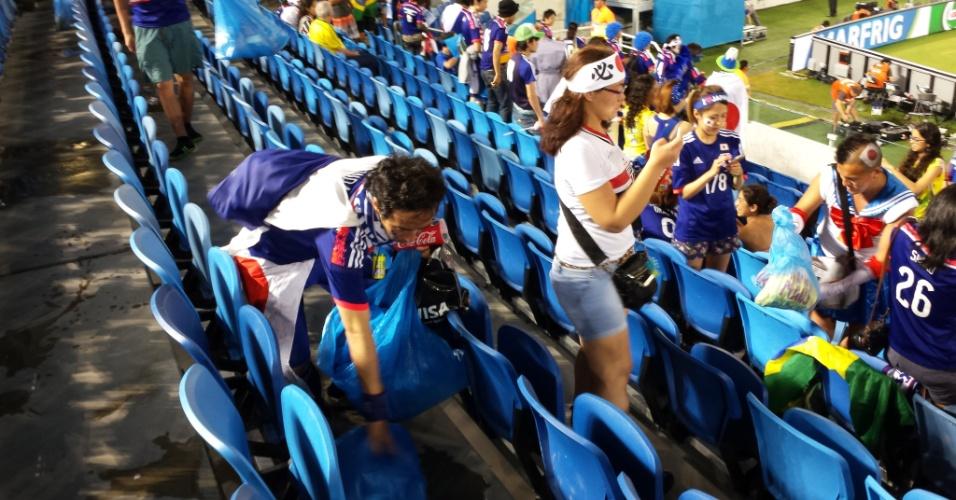 Torcedor japonês se agacha para recolher lixo do chão da Arena das Dunas