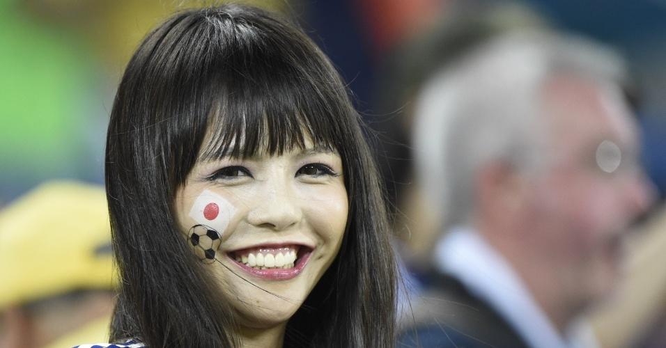 Torcedora japonesa sorri para a câmera durante jogo entre Japão e Grécia na Arena das Dunas