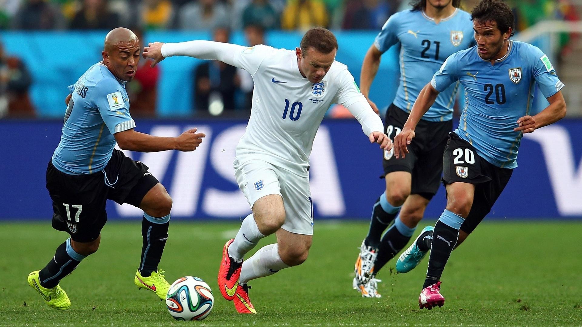 19.jun.2014 - Vaiado antes do jogo pela torcida no Itaquerão, inglês Wayne Rooney tenta escapar da marcação uruguaia