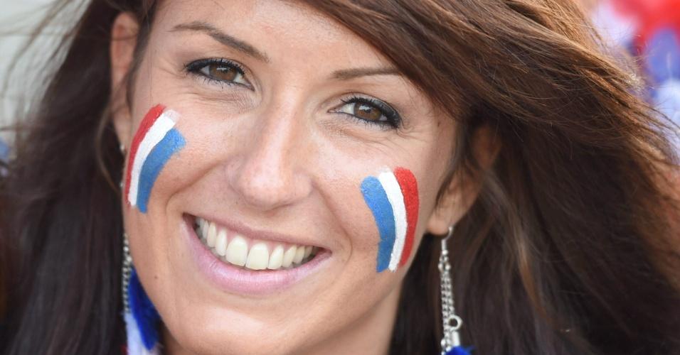 Torcedora com rosto pintado com as cores da França aguarda a partida contra a Suíça