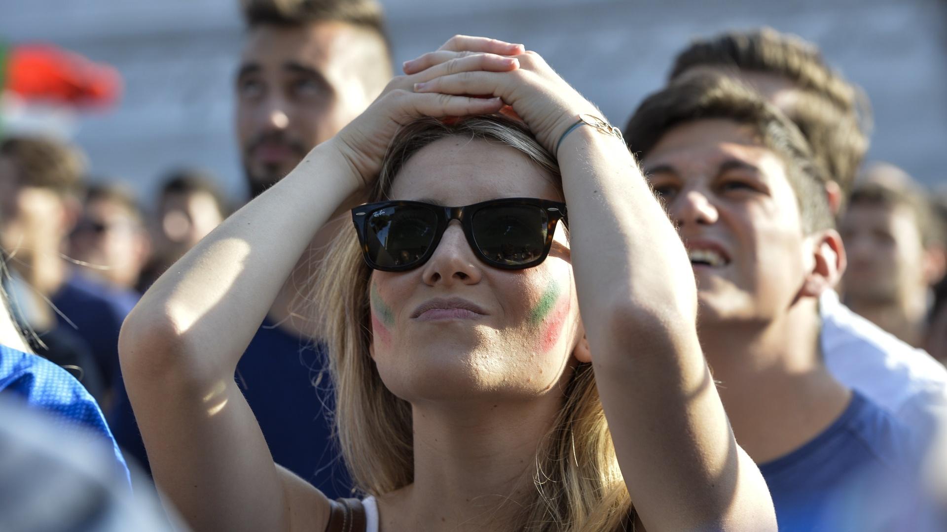 Torcedoras italianas sofrem ao torcer contra a Costa Rica em meio a uma multidão na Piazza Venezia, em Roma