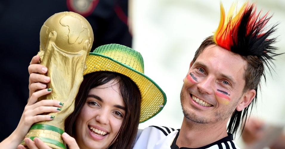 21.jun.2014 - Brasileira e alemão seguram réplica da taça da Copa antes do jogo entre Alemanha e Gana, no Castelão