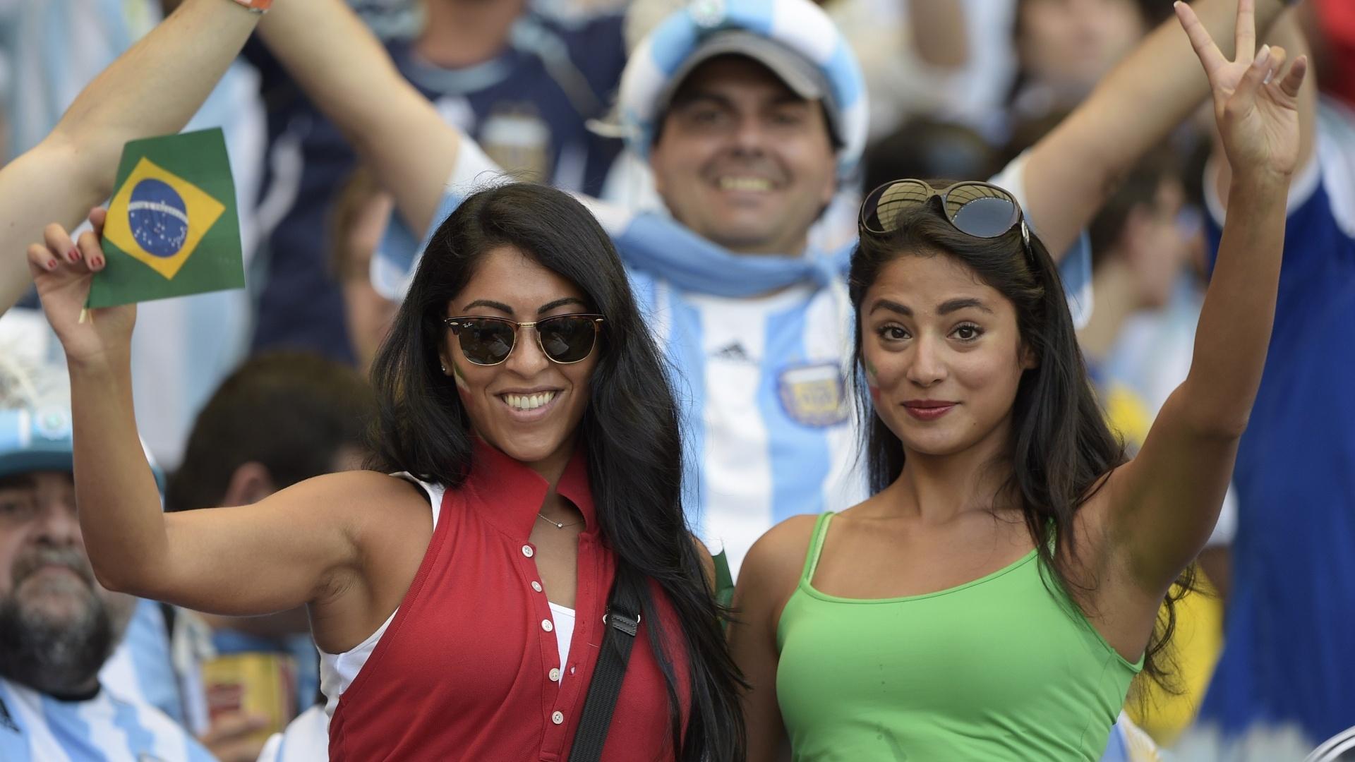 Com a bandeira do Brasil na mão e a do Irã no rosto, belas torcedores assistem ao jogo contra a Argentina no Mineirão