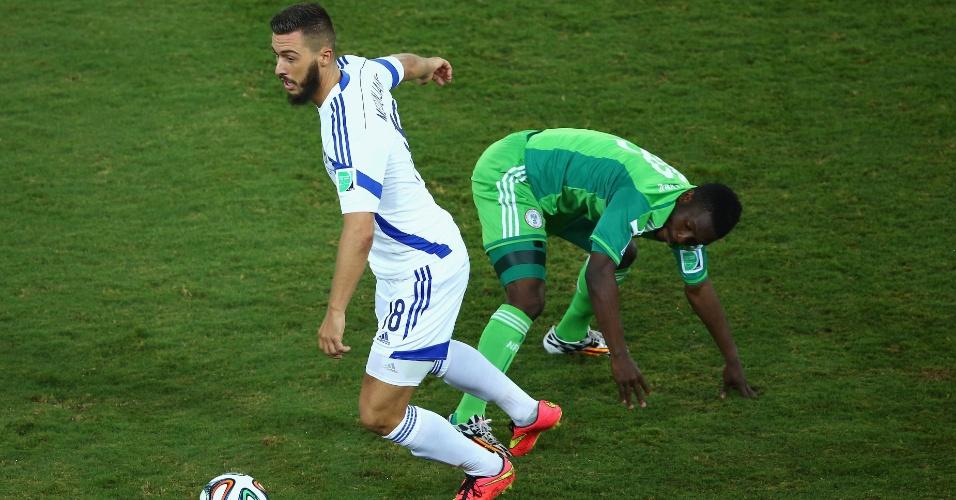 Haris Medunjanin, da Bósnia, dá sequência ao lance enquanto Michael Babatunde, da Nigéria, se apóia no gramado para continuar de pé