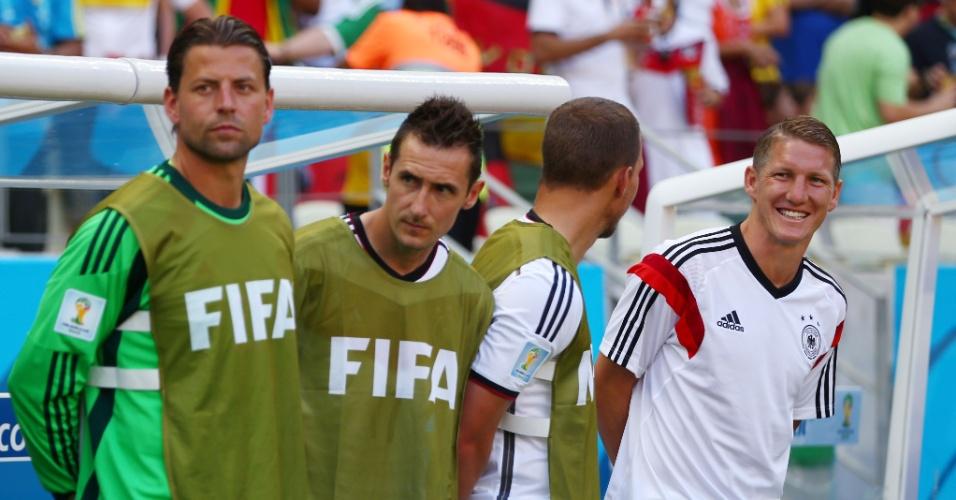 21.jun.2014 - Schweinsteiger (à direita) sorri no banco de reservas da Alemanha antes do jogo contra Gana, no Castelão