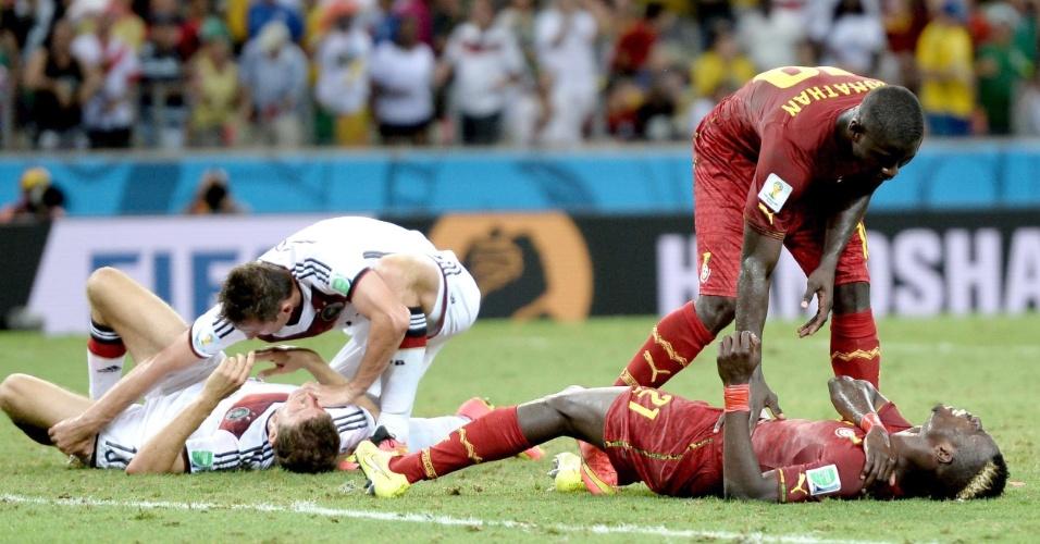 21.jun.2014 - Thomas Müller, da Alemanha, e John Boye, de Gana, ficam caídos no gramado após dividida no último lance do empate por 2 a 2
