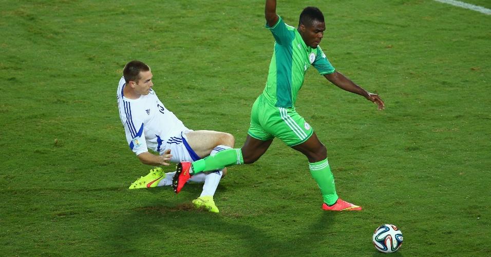 Toni Sunjic, da Bósnia, fica no chão enquanto Emmanuel Emenike, da Nigéria, segue com a bola