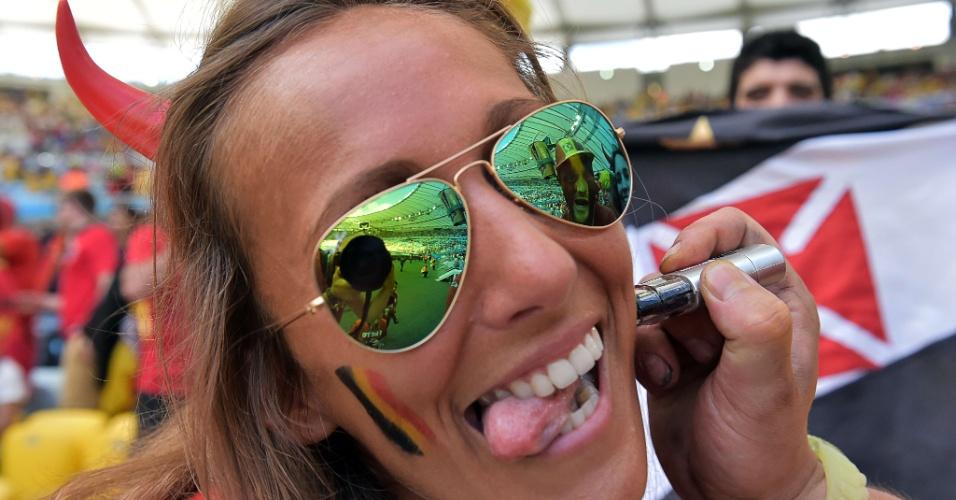 Torcedora pinta o rosto com a bandeira da Bélgica no Maracanã