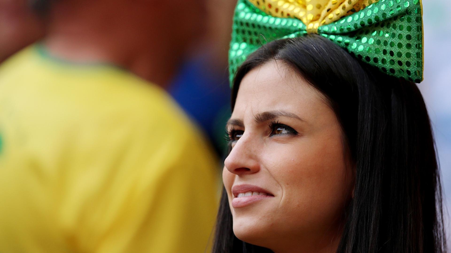 23.jun.2014 - Com um laço na cabeça, torcedora brasileira sorri enquanto aguarda o confronto contra Camarões