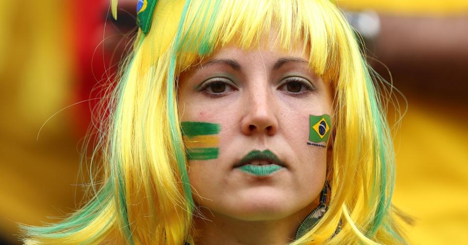 23.jun.2014 - Torcedora com as cores do Brasil aguarda o início da partida contra Camarões, em Brasília