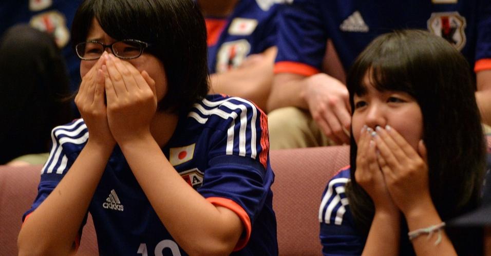24.jun.2014 - Em Tóquio, torcedoras japonesas ficar perto de irem às lágrimas após eliminação precoce da seleção na Copa