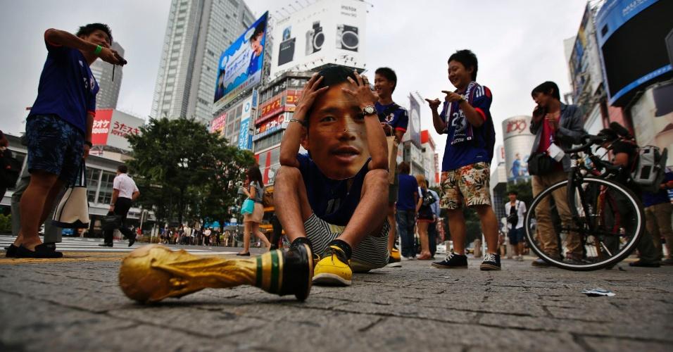 24.jun.2014 - Japonês com máscara do lateral Nagatomo brinca com a eliminação da seleção nacional na primeira fase da Copa do Mundo