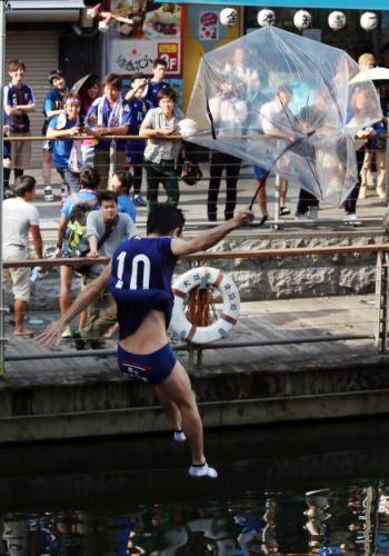 24.jun.2014 - Torcedor do Japão pula de guarda-chuva em rio da cidade de Osaka após derrota da seleção nacional para a Colômbia