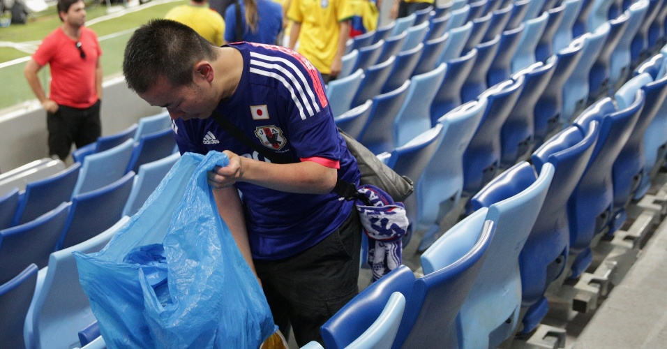 24.jun.2014 - Mesmo com a derrota e a eliminação do Japão, torcedor recolhe lixo na arquibancada da Arena Pantanal, depois da vitória colombiana por 4 a 1