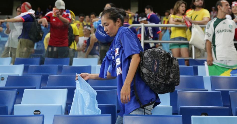 24.jun.2014 - Mesmo triste com a derrota do Japão, torcedora recolhe o lixo na arquibancada da Arena Pantanal