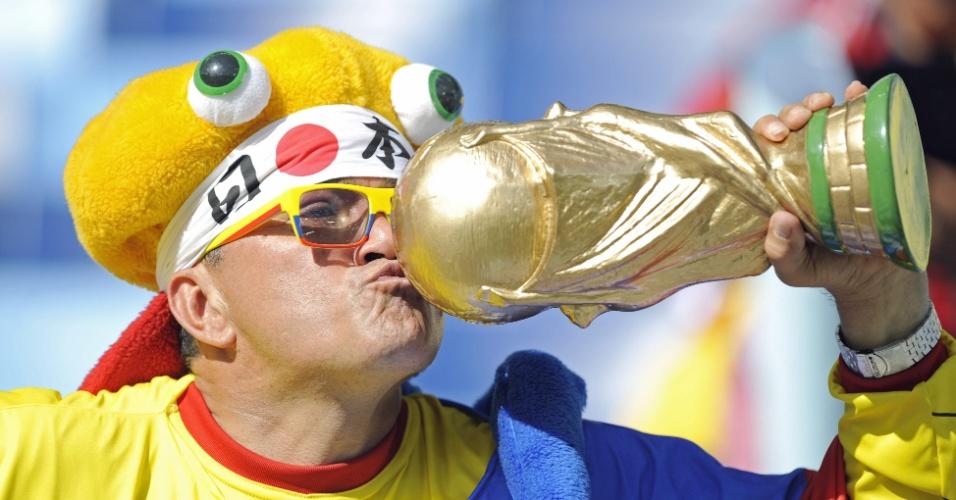 24.jun.2014 - Torcedor beija réplica da taça da Copa do Mundo na Arena Pantanal, antes do jogo entre Japão e Colômbia