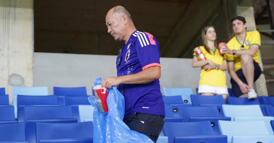 24.jun.2014 - Torcedor japonês separa o lixo na arquibancada da Arena Pantanal, após a derrota para a Colômbia por 4 a 1