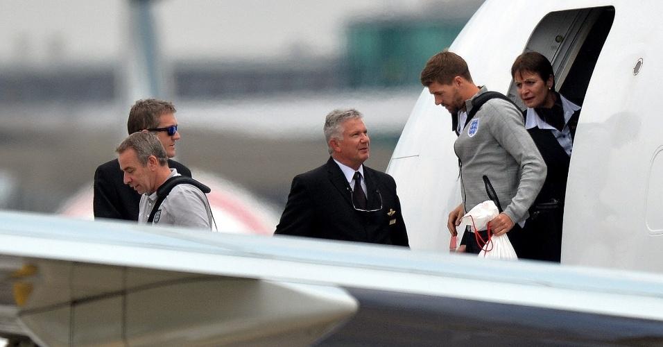 Steven Gerrard chega ao aeroporto de Manchester com a delegação inglesa após eliminação precoce na Copa do Mundo