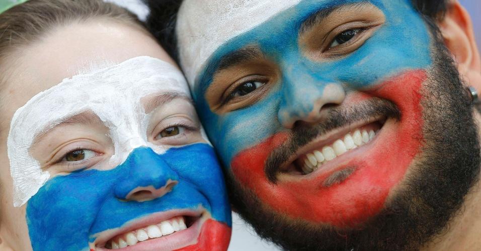 Casal russo pinta o rosto com as cores da bandeira e torce unido contra a Argélia, na Arena da Baixada