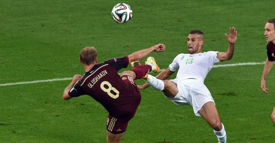 Islam Slimani, da Argélia, e Denis Glushakov, da Rússia, dividem a bola durante a partida na Arena da Baixada