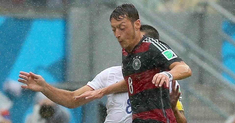 26.jun.2014 - Özil, da Alemanha, e Clint Dempsey, dos EUA, encaram a chuva na Arena Pernambuco