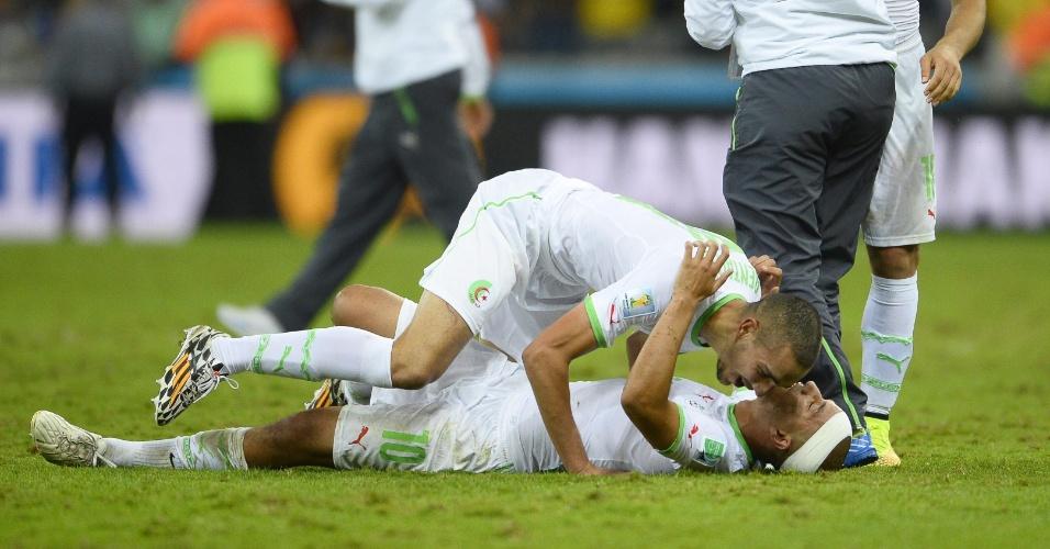 Sofiane Feghouli e Nabil Bentaleb caem no gramado e comemoram a classificação da Argélia para as oitavas de final da Copa do Mundo. A equipe empatou por 1 a 1 com a Rússia na Arena da Baixada