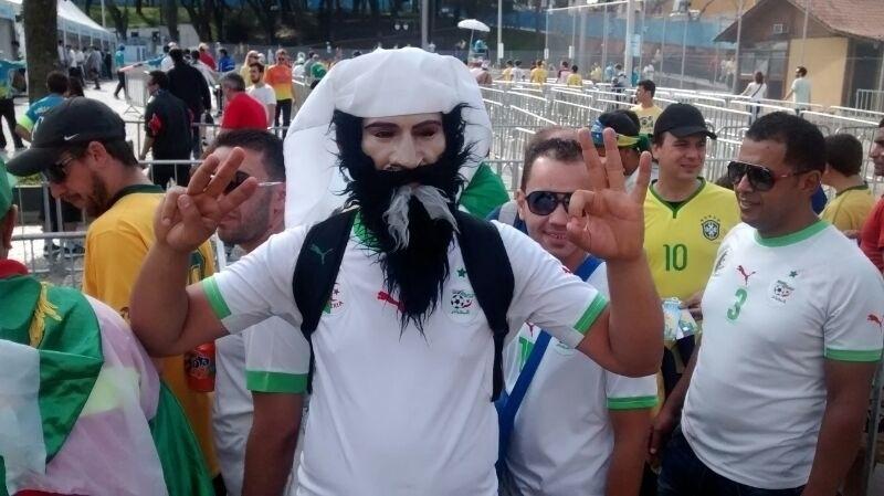 Torcedor usa máscara de árabe barbado para torcer pela Argélia contra a Rússia, na Arena da Baixada