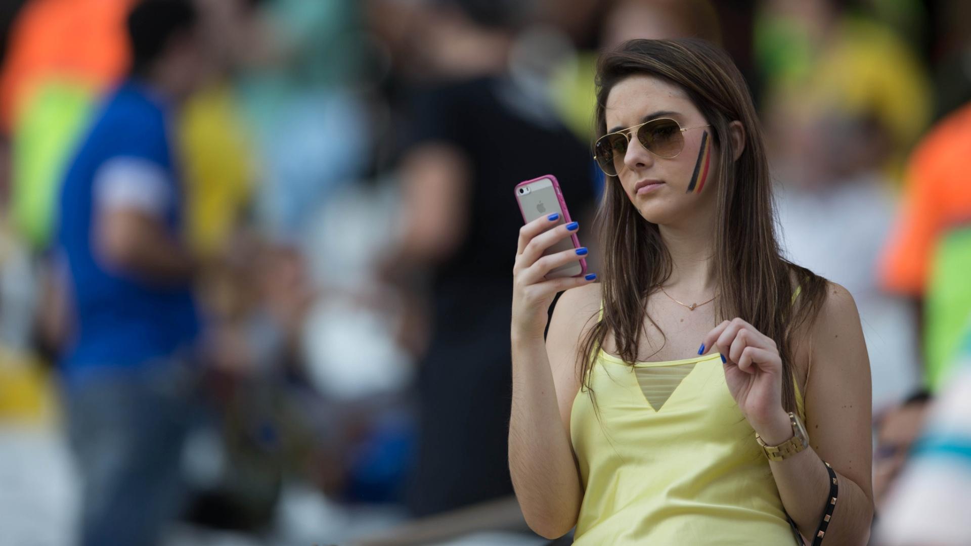 Torcedora olha para o celular antes do jogo entre Bélgica e Coreia do Sul no Itaquerão