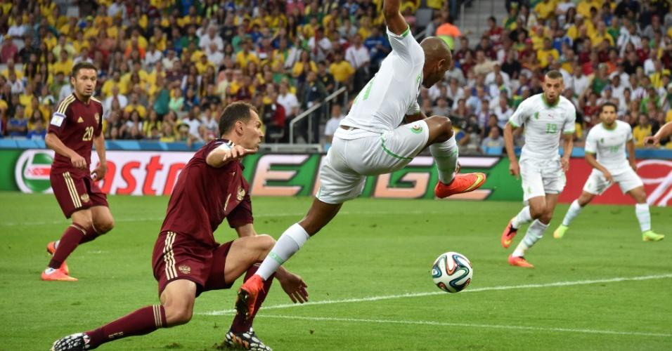 Yacine Brahimi, da Argélia, tenta cruzar a bola, mesmo estando por Ignashevich, da Rússia, na Arena da Baixada