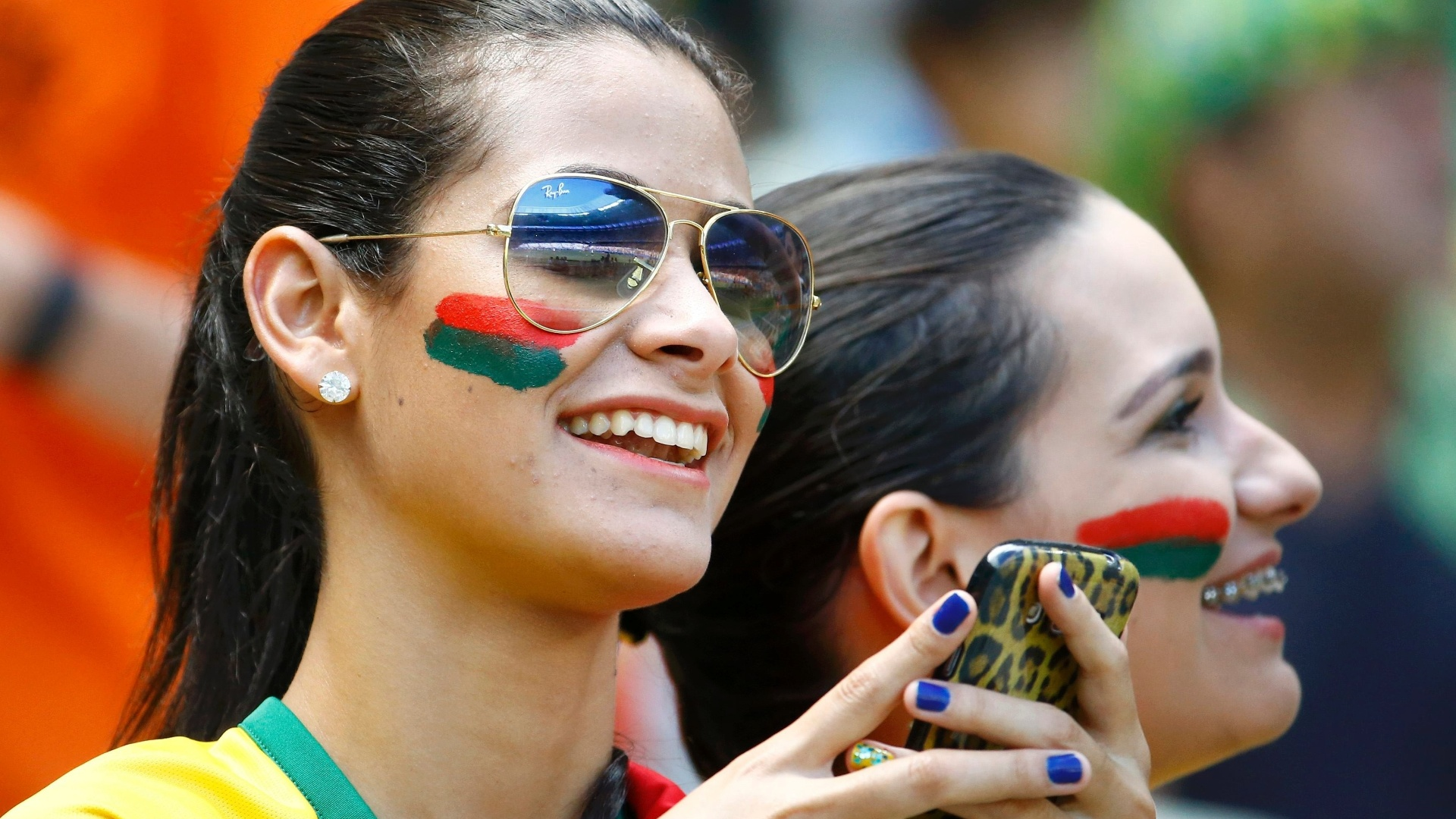 Brasileiras pintam o rosto com as cores do México para o jogo contra a Holanda no Castelão
