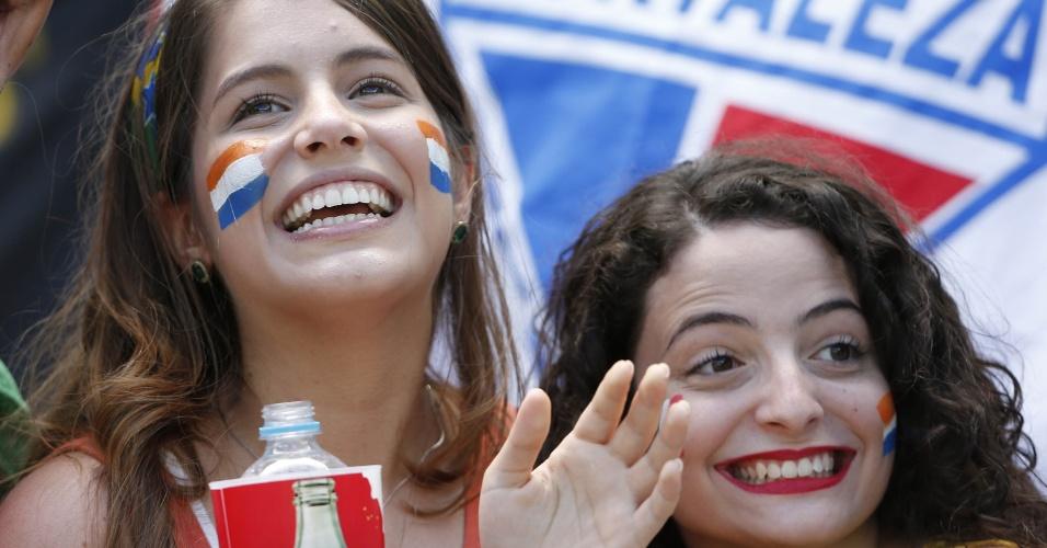 Com a bandeira do Fortaleza ao fundo, torcedoras com as cores da Holanda assistem ao jogo contra o México