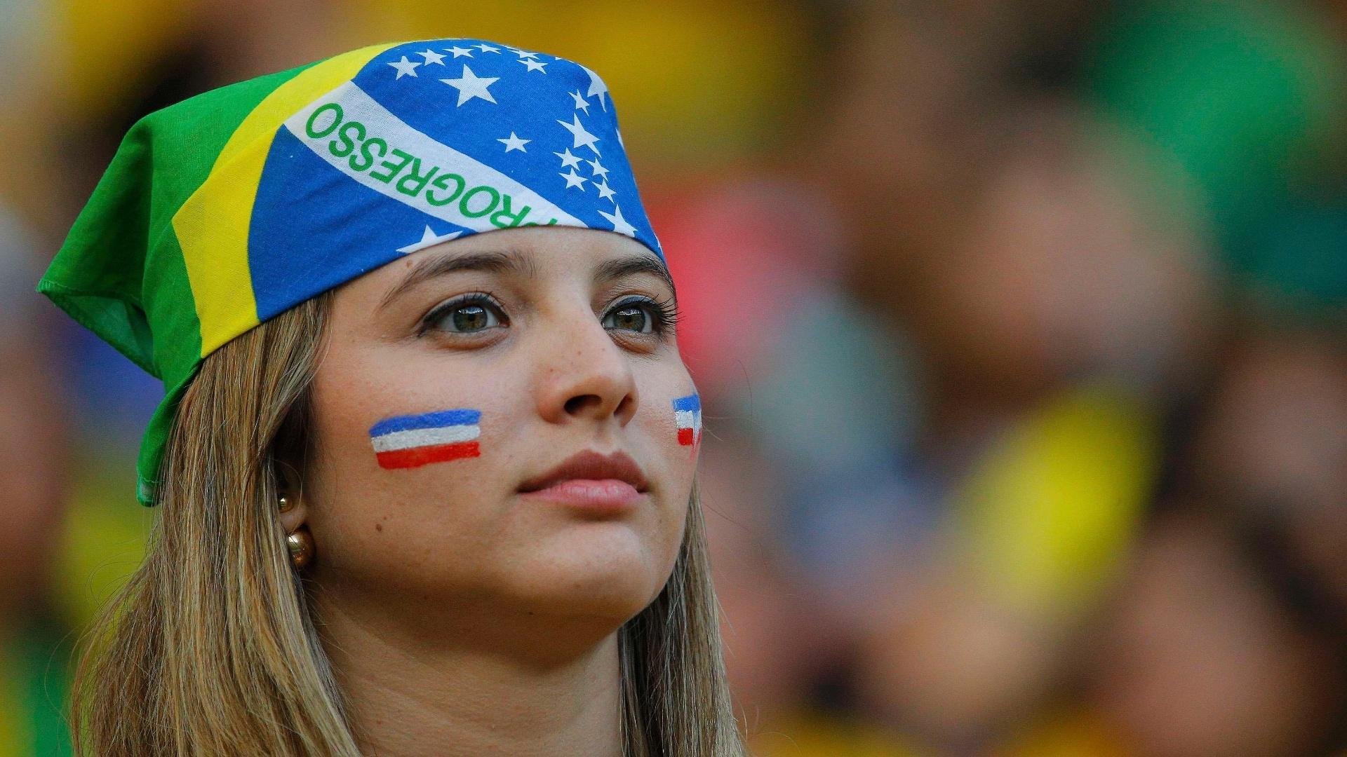 Torcedora com a bandana do Brasil pinta a bandeira da Costa Rica no rosto na Arena Pernambuco