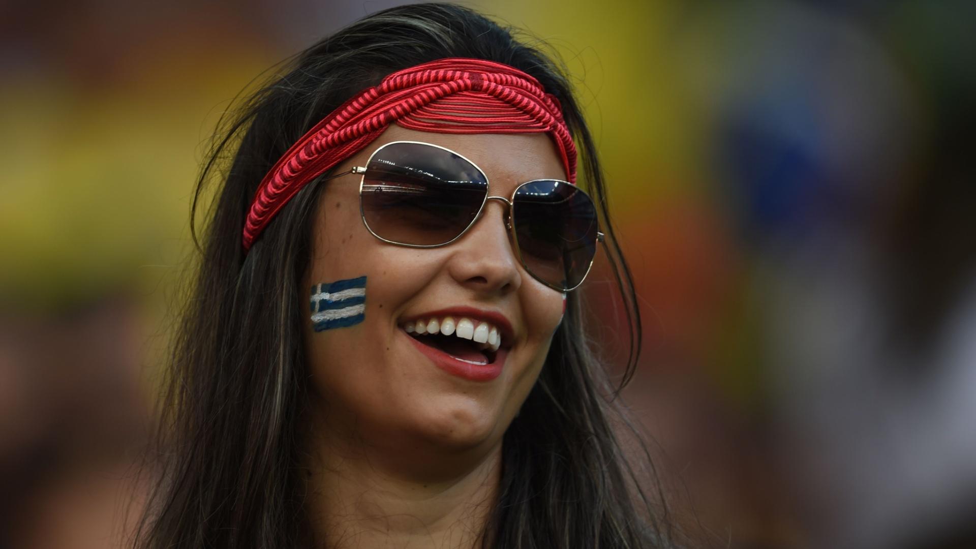 Torcedora com o rosto pintado sorri antes do jogo entre Grécia e Costa Rica na Arena Pernambuco