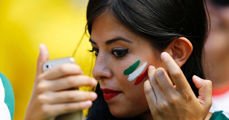 Torcedora mexicana usa celular como espelho para pintar o rosto com as cores do país