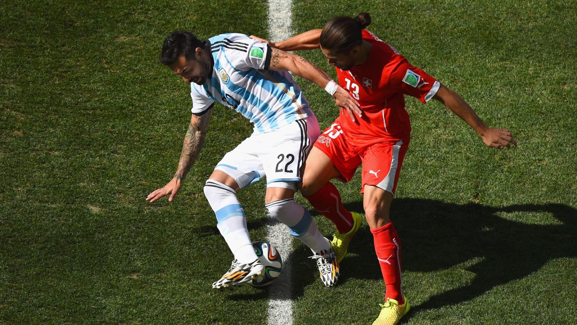01.jul.2014 - Argentino Lavezzi disputa a bola com Ricardo Rodriguez, da Suíça, no início do jogo no Itaquerão, válido pelas oitavas de final
