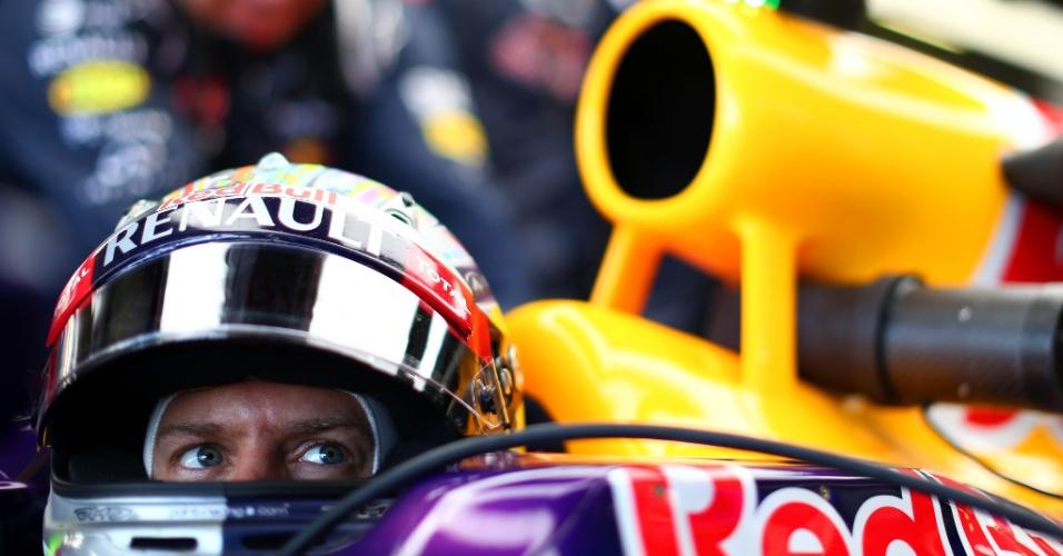 Vettel observa monitores no box da Red Bull enquanto não tem aval para ir à pista em treino no circuito de Silverstone, na Inglaterra