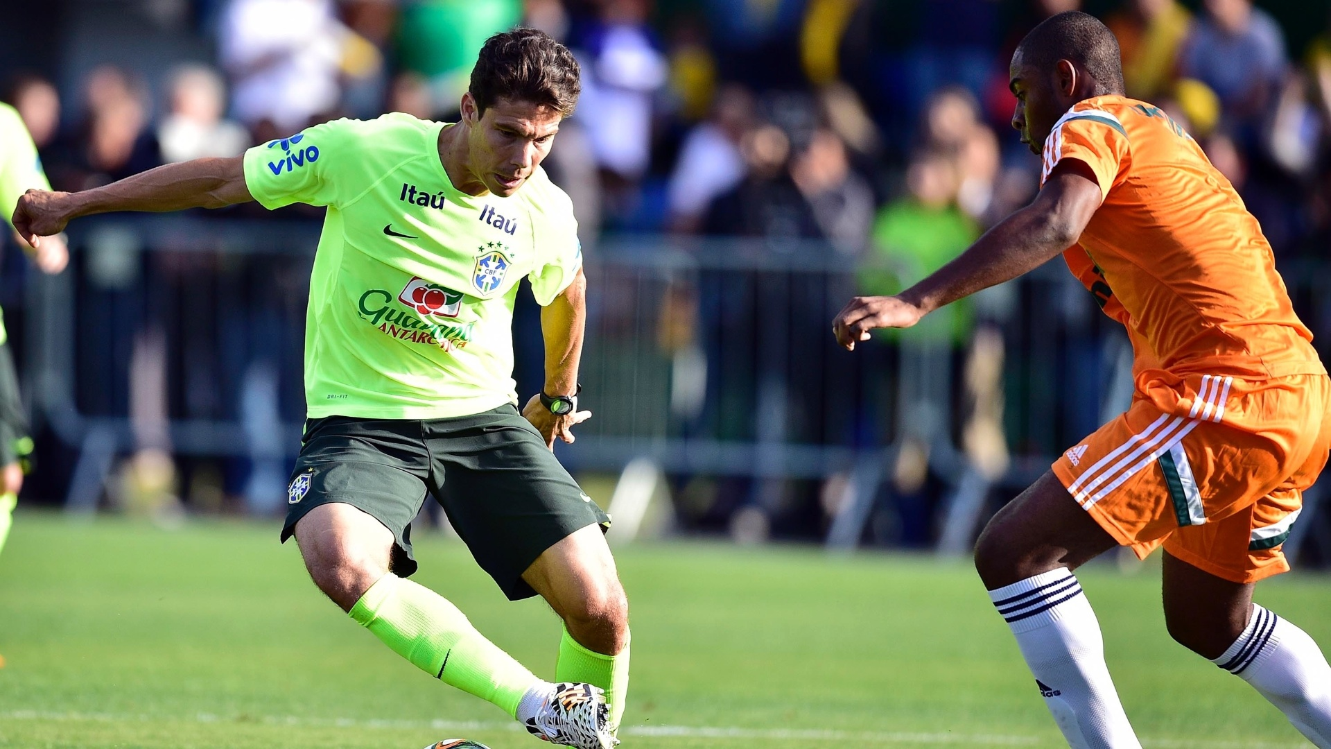 06.jul.2014 - Meia Hernanes tenta passar pela marcação durante treino da seleção contra o time sub-20 do Fluminense