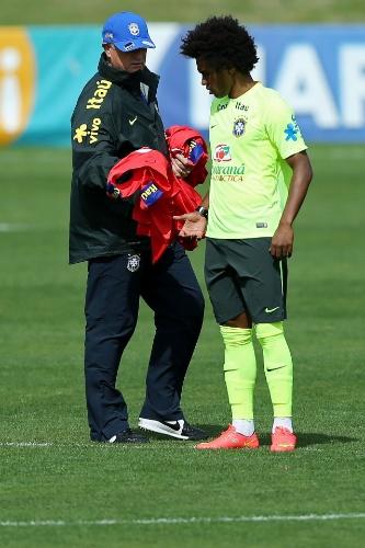 07.jul.2014 - Felipão dá colete de reserva a Willian no início do treino do Brasil na Granja Comary