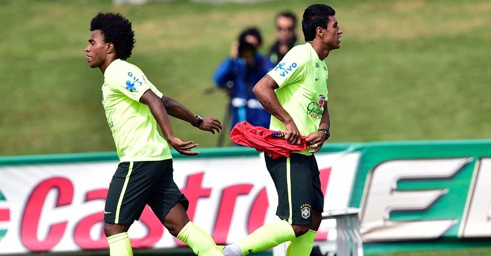 07.jul.2014 - Willian passa o colete de reserva a Paulinho em uma das mudanças feitas por Felipão no time durante treino desta segunda (07/07)
