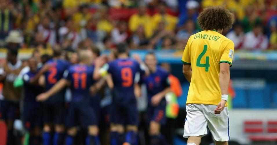 12.jul.2014 - David Luiz lamenta enquanto jogadores da Holanda comemoram gol na vitória por 3 a 0 no estádio Mané Garrincha