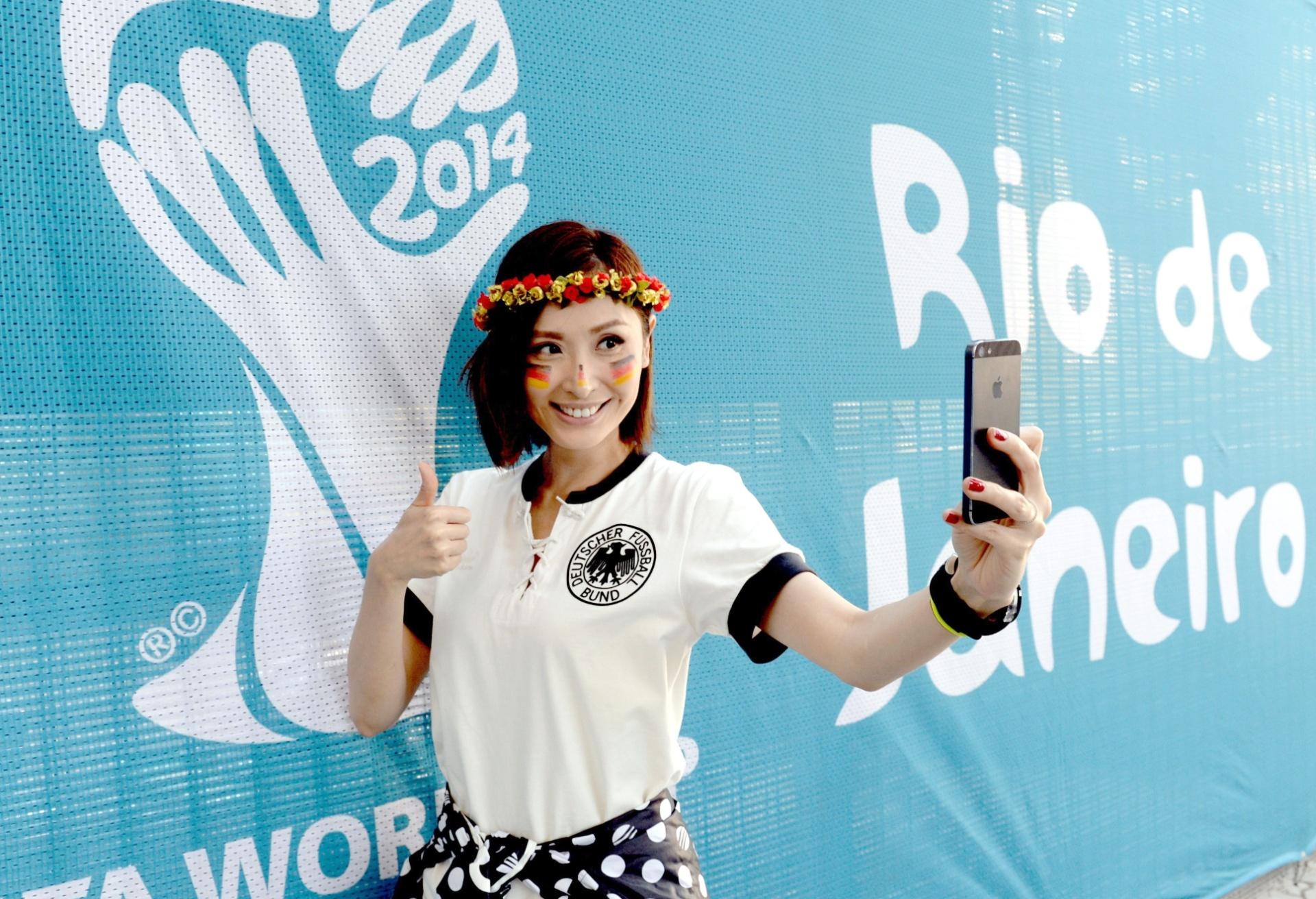 Toda produzida para a final da Copa do Mundo, torcedora da Alemanha faz selfie em frente a painel da taça do mundo