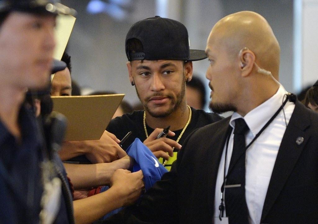 31.jul.2014 - Com caneta na mão, Neymar se prepara para distribuir autógrafos aos fãs japoneses que o aguardavam em aeroporto de Tóquio