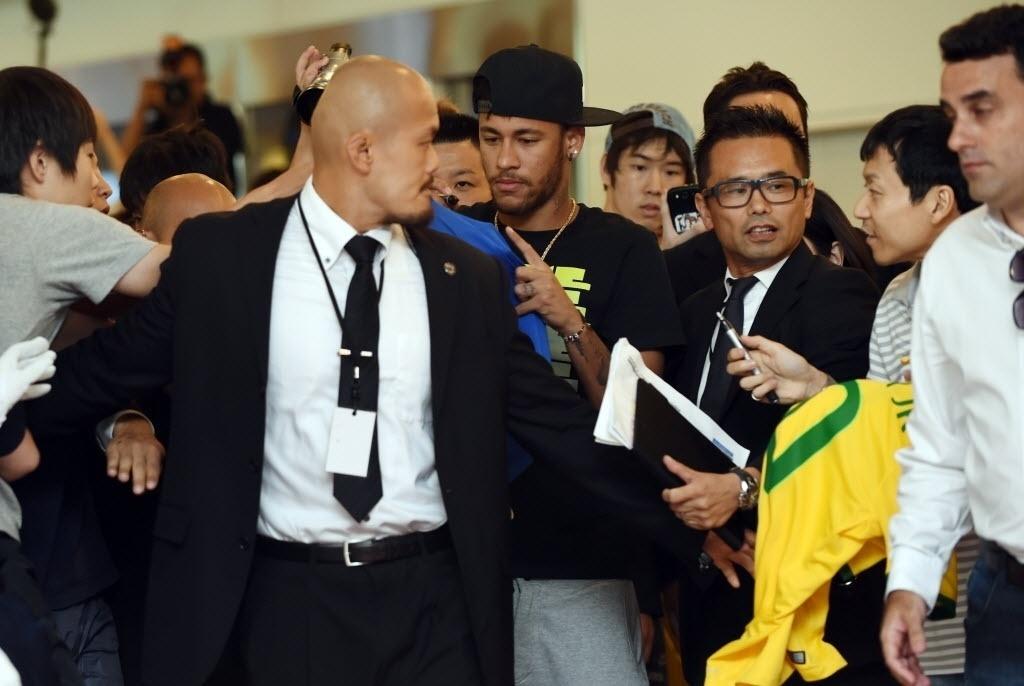 31.jul.2014 - Neymar apoia em segurança para assinar camisa de fã japonês na sua recepção em Tóquio