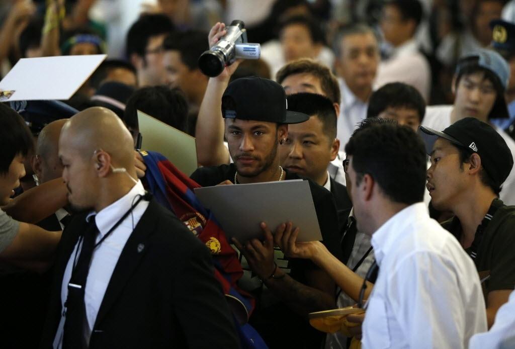 31.jul.2014 - Neymar dá autógrafo para fã japonês em meio a multidão que o recebeu no aeroporto de Tóquio, no Japão