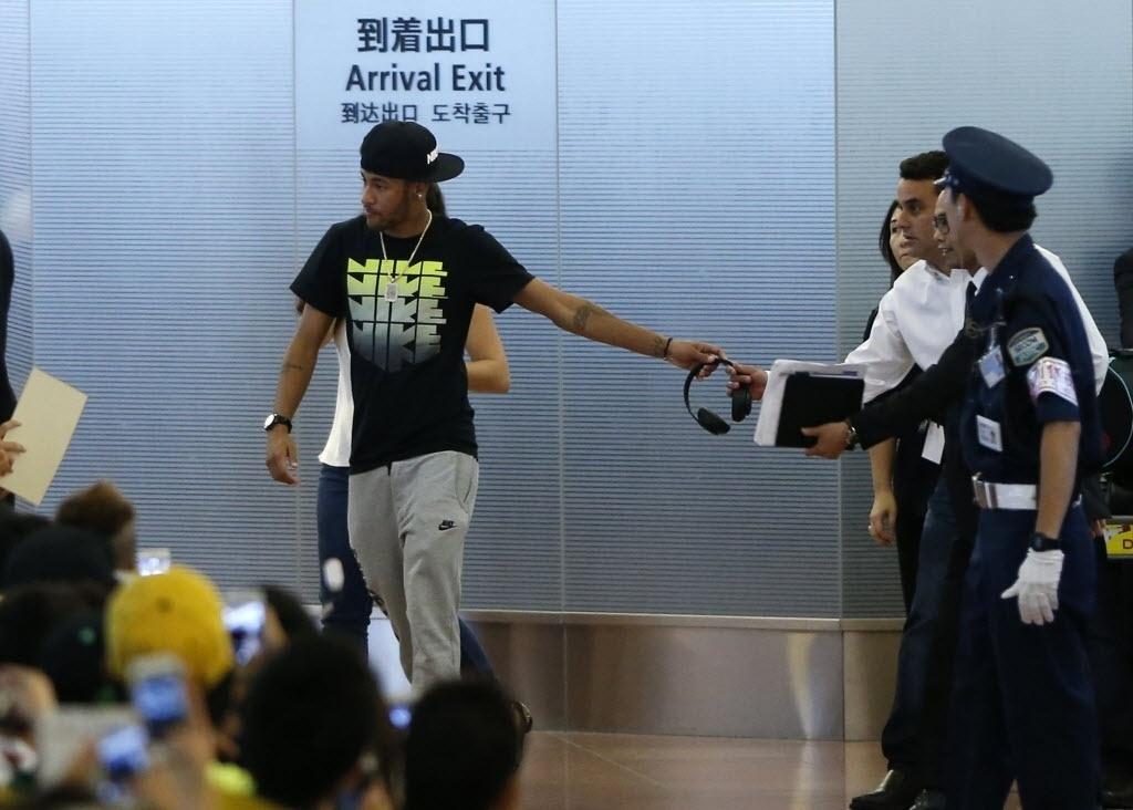 31.jul.2014 - Neymar deixa seus pertences com estafe para poder atender a multidão de fãs que o esperava em aeroporto de Tóquio
