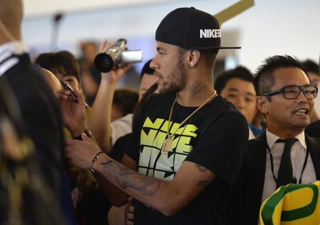 31.jul.2014 - Neymar distriui autógrafos para fãs japoneses no seu desembarque em Tóquio